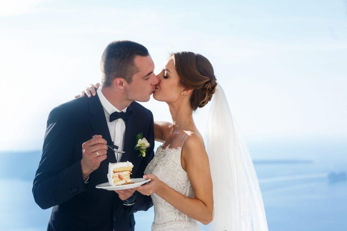 Happy bride and groom eating delicious wedding cake closeup