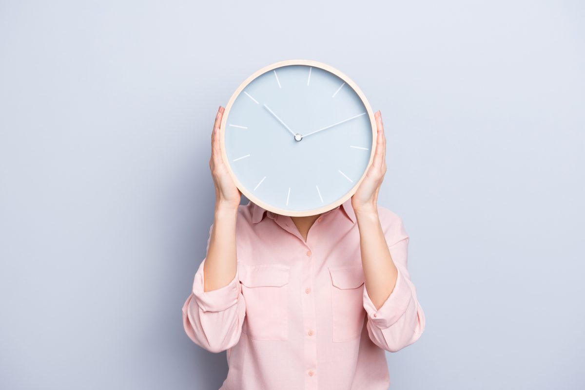 It's 10:10 o'clock. Portrait of charming pretty positive cheerful woman closing covering head face with round clock isolated on grey background